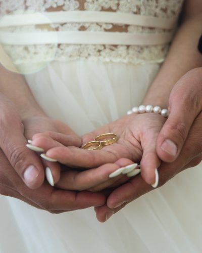 Two golden wedding rings on bride and groom's palms. Wedding rin